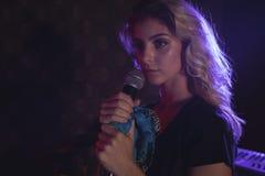 Fermez-vous de la belle chanteuse avec le microphone photos libres de droits