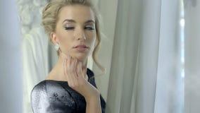 Fermez-vous de la belle femme utilisant les boucles d'oreille brillantes de diamant regardant la fenêtre attendant quelqu'un banque de vidéos