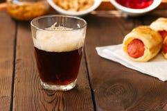 Fermez-vous de la bière foncée dans un verre avec des porcs dans une couverture, ketchup image libre de droits