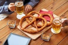 Fermez-vous de la bière potable de l'homme avec des bretzels au bar Image libre de droits