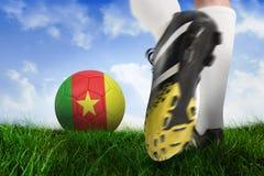 Fermez-vous de la botte du football donnant un coup de pied la boule du Cameroun Photographie stock libre de droits