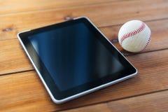 Fermez-vous de la boule de base-ball et du PC de comprimé sur le bois Photos libres de droits