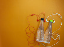 fermez-vous de la bouteille d'eau et des écouteurs sur le CCB orange de papier de couleur Images libres de droits