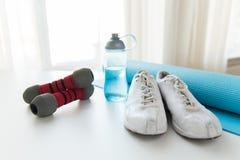 Fermez-vous de la bouteille, des haltères, des espadrilles et du tapis Image stock