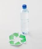 Fermez-vous de la bouteille en plastique et symbole de réutilisation Image stock