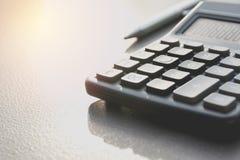 Fermez-vous de la calculatrice noire avec le stylo et copiez l'espace technologie Photos stock