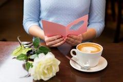 Fermez-vous de la carte de voeux et du café de lecture de femme Photos stock