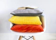 Fermez-vous de la chaise dans un intérieur avec des oreillers dans le colo à la mode Photo stock