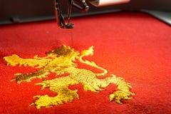 Fermez-vous de la conception de lion de machine et d'or de broderie sur le tissu rouge Images stock