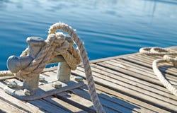 Fermez-vous de la corde attachée sur un bitt sur le dock en bois Images libres de droits