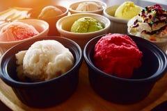 Fermez-vous de la crème glacée colorée de table dans la petite tasse placée sur le bois de brun de plateau Photos stock