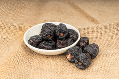 Fermez-vous de la cuillère en bois avec des fruits de dattes sèches se trouvant sur la toile à sac Photographie stock