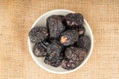 Fermez-vous de la cuillère en bois avec des fruits de dattes sèches se trouvant sur la toile à sac Photos libres de droits