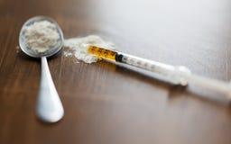 Fermez-vous de la cuillère et de la seringue avec la dose de drogue photos stock