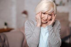 Fermez-vous de la dame âgée avec le mal de tête Image libre de droits