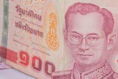 Fermez-vous de la devise de la Thaïlande, baht thaïlandais avec les images du roi de la Thaïlande Dénomination de 100 bahts Photographie stock libre de droits