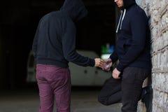 Fermez-vous de la dose de achat d'intoxiqué du trafiquant de drogue image libre de droits