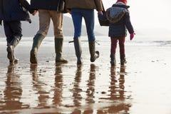 Fermez-vous de la famille marchant le long de la plage d'hiver Photo stock