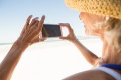 Fermez-vous de la femme à l'aide du téléphone intelligent tout en se tenant contre le ciel Image stock
