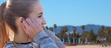 Fermez-vous de la femme écoutant la musique dans des écouteurs image libre de droits