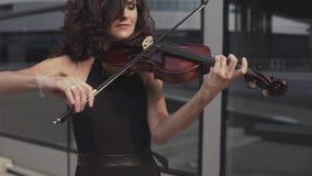 Fermez-vous de la femme élégante dans la robe noire jouant le violon près du bâtiment en verre banque de vidéos