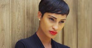 Fermez-vous de la femme africaine dans la robe noire et le rouge à lèvres rouge se penchant contre le mur image libre de droits