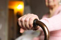 Fermez-vous de la femme agée tenant une canne de marche dans la maison de repos Photographie stock