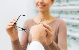 Fermez-vous de la femme avec des verres au magasin d'optique photos stock