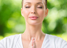 Fermez-vous de la femme avec faire des gestes de prière fermé par yeux photo stock