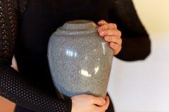 Fermez-vous de la femme avec l'urne d'incinération à l'enterrement image libre de droits