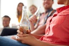 Fermez-vous de la femme avec la bouteille et les amis à bière Photographie stock libre de droits