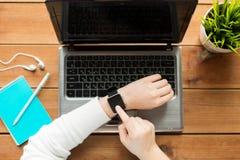 Fermez-vous de la femme avec la montre et l'ordinateur portable intelligents photo stock