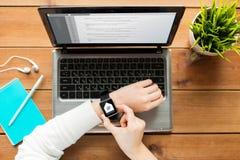 Fermez-vous de la femme avec la montre et l'ordinateur portable intelligents photographie stock