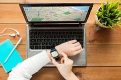 Fermez-vous de la femme avec la montre et l'ordinateur portable intelligents photo libre de droits