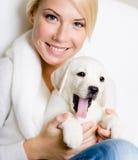 Fermez-vous de la femme avec le chiot de Labrador sur ses genoux images stock