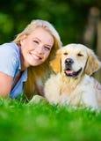 Fermez-vous de la femme avec le golden retriever sur l'herbe Images libres de droits