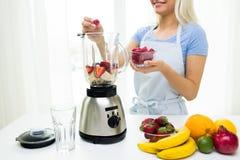 Fermez-vous de la femme avec le mélangeur faisant la secousse de fruit Photo libre de droits