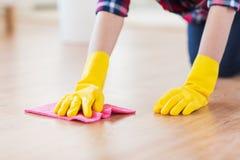 Fermez-vous de la femme avec le plancher de nettoyage de chiffon à la maison image libre de droits