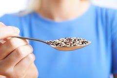 Fermez-vous de la femme avec le quinoa sur la cuillère photos stock