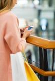 Fermez-vous de la femme avec le smartphone et le panier Images libres de droits