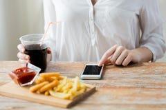Fermez-vous de la femme avec le téléphone intelligent et les aliments de préparation rapide Image stock
