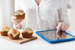 Fermez-vous de la femme avec les petits gâteaux et le PC de comprimé Photo libre de droits