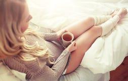Fermez-vous de la femme avec la tasse de thé dans le lit Photo stock