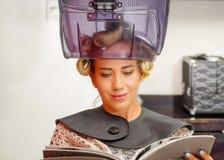 Fermez-vous de la femme blonde lisant un livre et attendant sous un vieux capot de chaise de cheveu-dessiccateur, à un arrière-pl image stock
