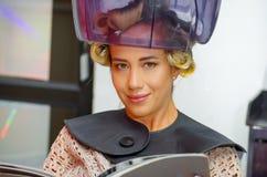Fermez-vous de la femme blonde de sourire lisant un livre et attendant sous un vieux capot de chaise de cheveu-dessiccateur, à un photographie stock