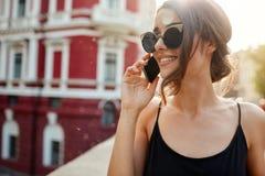 Fermez-vous de la femme caucasienne attirante gaie avec les cheveux foncés dans les lunettes de soleil et la robe noire parlant a image libre de droits