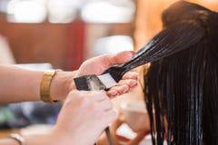Fermez-vous de la femme de coiffeur appliquant des soins capillaires avec un peigne son client santé images libres de droits