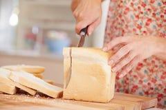Fermez-vous de la femme coupant en tranches la miche de pain dans la cuisine Photos libres de droits