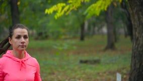 Fermez-vous de la femme courant par un parc d'automne au coucher du soleil Mouvement lent banque de vidéos