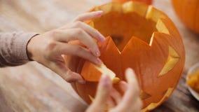 Fermez-vous de la femme découpant le potiron de Halloween clips vidéos